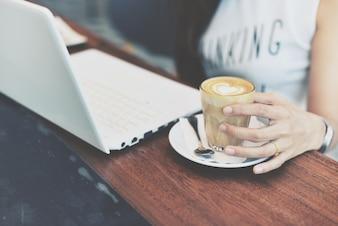 Mão da mulher segurando um copo com copo de café