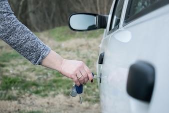 Mão de mulher abrindo porta de carro com chave