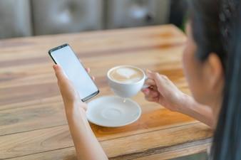 Mão de negócios com o telefone móvel e o café da arte latte.