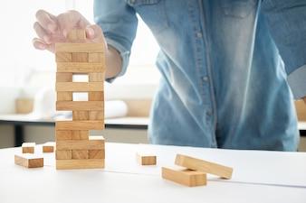 Mão de planejamento, risco e estratégia de negócios em negócios. Empresário jogando colocando bloco de madeira em uma torre.