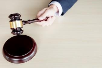Mão do martelo de madeira do juiz segurando um martelo contra o fundo de madeira