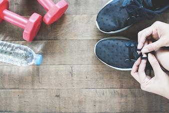 Mão feminina ativa com equipamentos desportivos e de trabalho, apartamento deitado no chão de madeira
