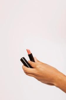Mão feminina segurando um batom