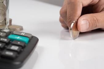 Mão humana segurando uma moeda e espaço para cópia, conceito de plano de investimento empresarial.