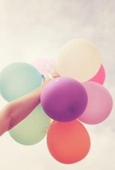 Mão segurando balões multicolores com efeito de filtro retro
