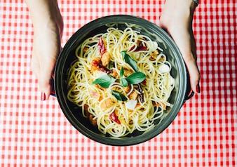 Mão segurando espaguete caseiro na toalha de mesa