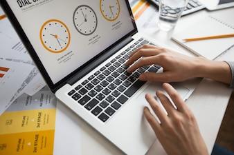 Mãos da mulher de negócios usando o portátil no escritório