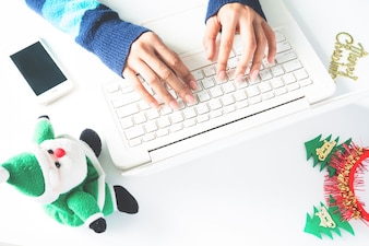 Mãos da mulher digitando no laptop do teclado, usando o smartphone com decoração de Natal, compras on-line