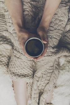 Mãos da mulher segurando café espresso quente saboroso em copo cerâmico sentado na cama com xadrez. Conceito de casa. Vista do topo.