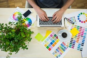 Mãos de designer gráfico macho usando laptop