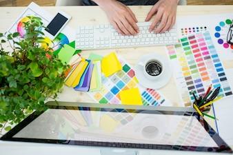Mãos do designer gráfico do sexo masculino usando o computador