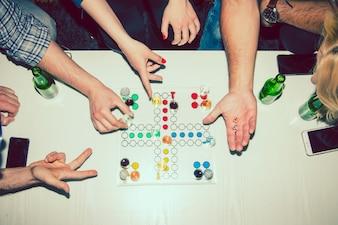 Mãos jogando com um boardgame na festa