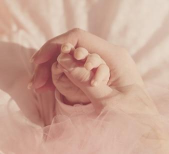 Mãos pequenas pequenas do bebê na mão da matriz. Fundo Cor-de-rosa. Pastel.