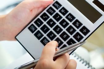 Mãos que prendem a calculadora