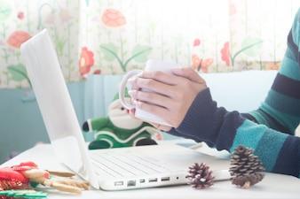 Mãos segurando xícara de café e usando laptop com decoração de Natal, compras on-line