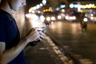 Mãos usando o smartphone de noite na rua da cidade