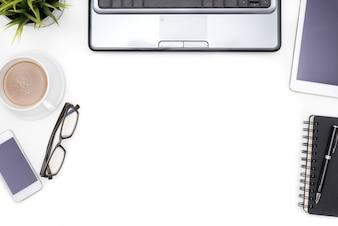 Material de escritório com caderno de computador na mesa branca