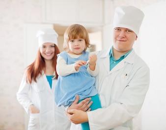 Médico e enfermeiro com criança na clínica