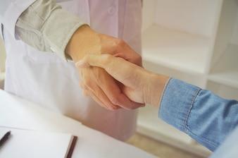 Médico segurando a mão do paciente e tranquilizando seu paciente masculino, ajudando o conceito de mão