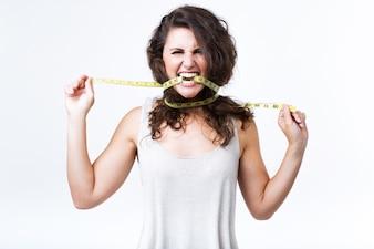Medida de fita madura da jovem mulher sobre o fundo branco.