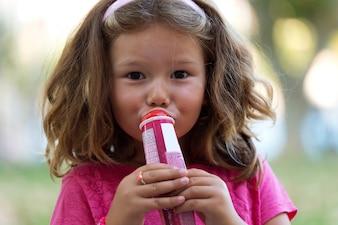 Menina adorável que come o gelado