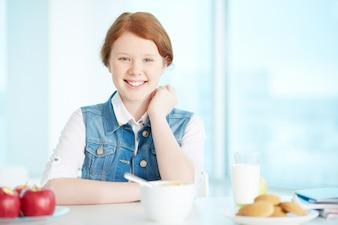 Menina alegre que tem o pequeno almoço em casa