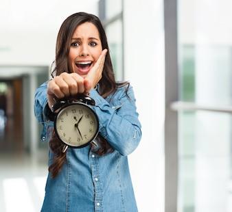 Menina apavorada segurando um relógio