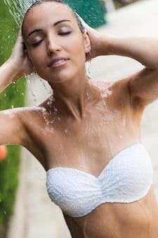 Menina bonita no chuveiro do verão perto da associação