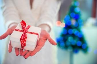 Menina bonita segurando um presente de Natal na frente dela. Mulher feliz no chapéu do papai noel que está perto da árvore do ano novo e que espera a celebração.