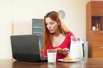 Menina bonito que verifica o e-mail no laptop durante o horário de café da manhã em casa