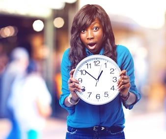 Menina choc com um grande relógio