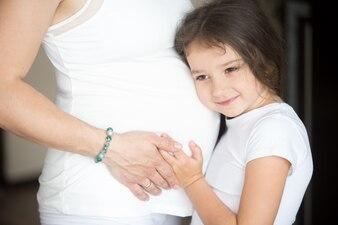 Menina com a cabeça apoiada em uma barriga grávida