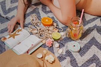 Menina com agenda e bebida na praia