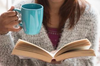 Menina com copo e livro aberto