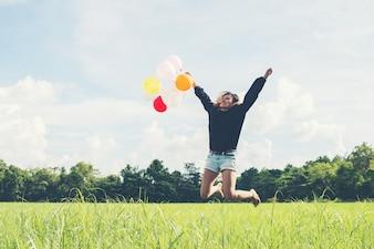 Menina com os balões coloridos que saltam