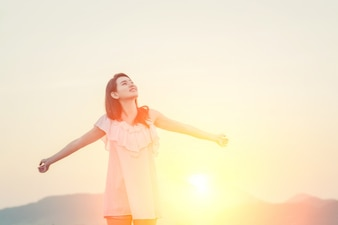 Menina com os braços esticados e o sol atrás