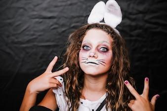 Menina com pintura de rosto de lebre posando