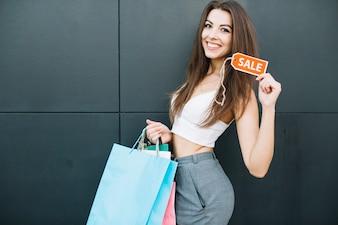 Menina com sinal de venda e sacolas de compras