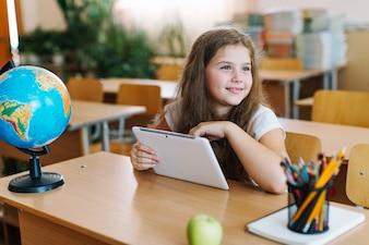 Menina com tablet na sala de aula