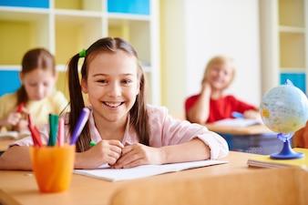 Menina com um grande sorriso em uma sala de aula