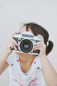 Menina com uma câmera velha da foto