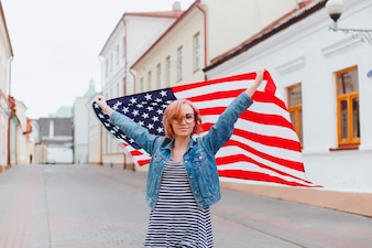 Menina com vidros de massas com uma bandeira americana