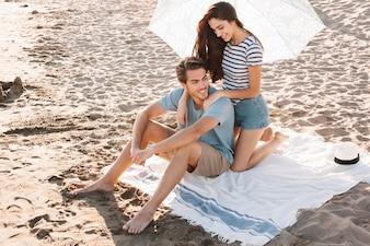 Menina dando massagem ao namorado na praia