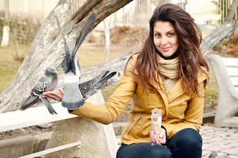 Menina de sorriso com pombos comendo em sua mão