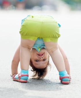 Menina de três anos jogando de cabeça para baixo