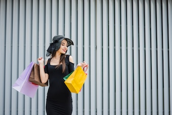 Menina de vestido preto com sacolas de compras