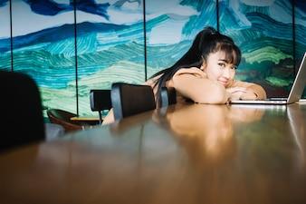 Menina deitada na mesa com laptop