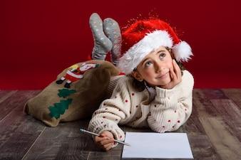 Menina deitada no chão pensativa com um lápis e um papel