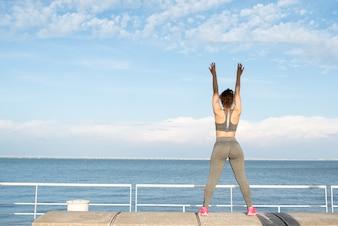 Menina desportiva que exercita no parapeito pelo rio
