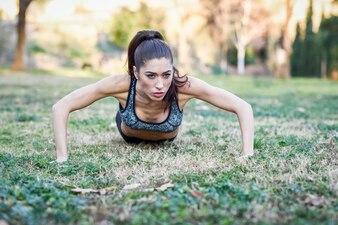 Menina desportiva que faz push-ups ao ar livre